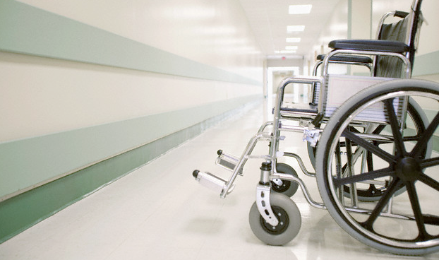 An empty wheelchair in an empty hospital hallway
